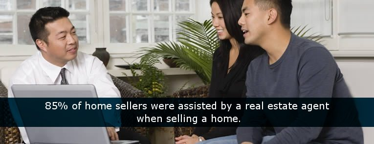 home sellers with real estate agent discussing the sale of their home